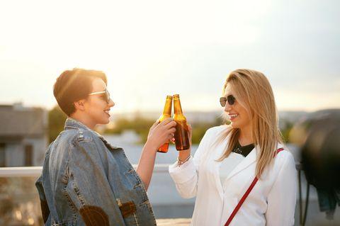 Zwei Freundinnen stoßen mit Bier an