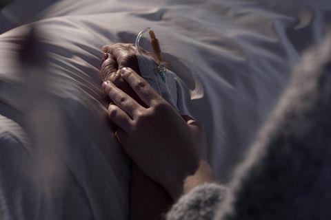 Abschied nehmen: Frau hält Hand eines Menschen am Sterbebett