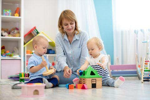 Kinderbetreuung: Kinder spielen mit Frau
