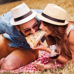 Ein Pärchen beißt gleichzeitig in ein Stück Pizza