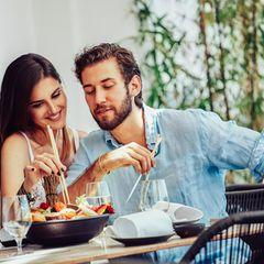 Eine Frau isst vom Teller ihres Partners