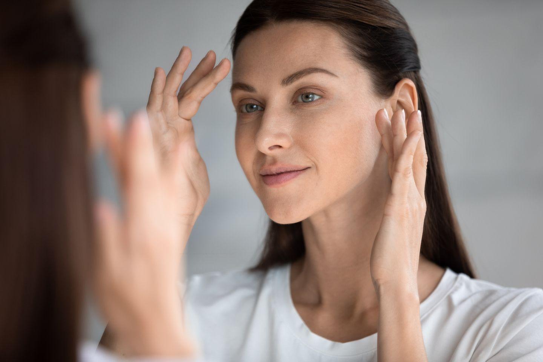 Brünette Frau betrachtet faltenfreie Haut im Spiegel