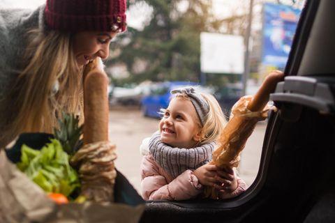 Mutter und Tochter räumen Einkauf aus dem Auto