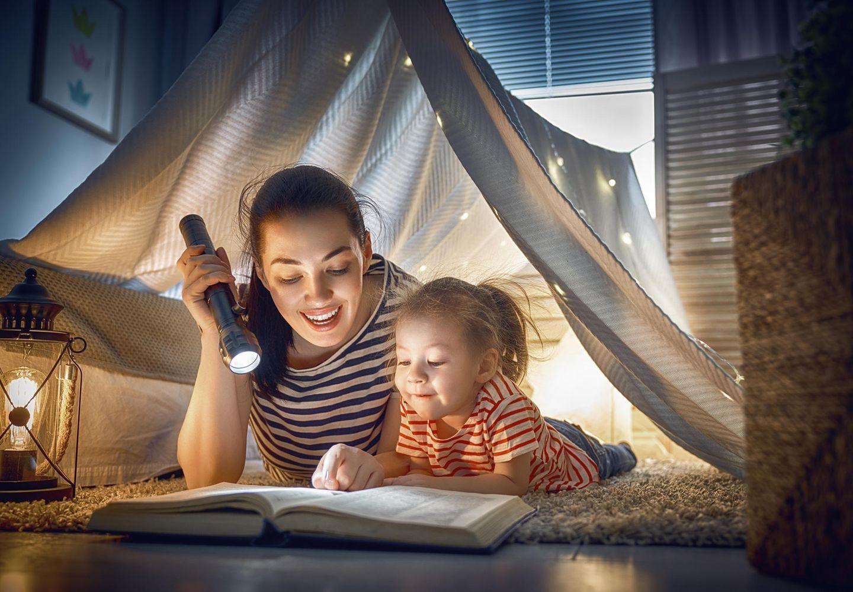Kinderbetreuung: Junge Frau liest Kind ein Buch vor