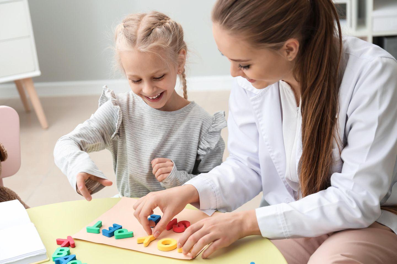 Kinderbetreuung: Frau spielt mit Mädchen