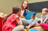 Kinderbetreuung: Junge Frau liest Kindern ein Buch vor