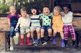 Kinderbetreuung: Sechs Kinder sitzen auf Bank