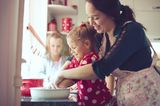Kinderbetreuung: Frau backt mit Kindern