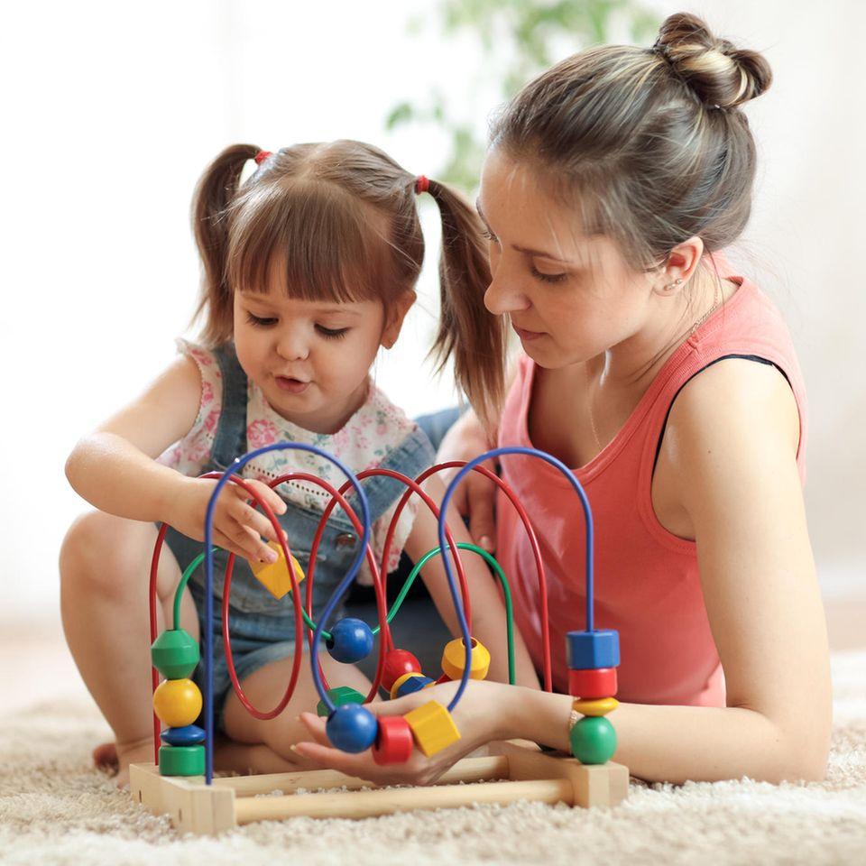 Kinderbetreuung: Junge Frau spielt mit Mädchen