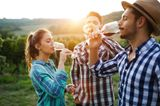 Eine Frau mit zwei Männern bei der Weinverkostung