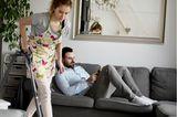 Eine Frau saugt Staub, während ihr Mann auf der Couch sitzt