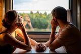 Ein Pärchen sitzt im Zug und schaut aus dem Fenster