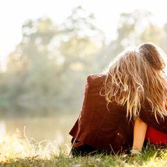 Zwei Freundinnen sitzen auf einer Wiese