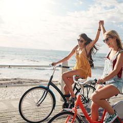 Zwei Freundinnen fahren zusammen Fahrrad