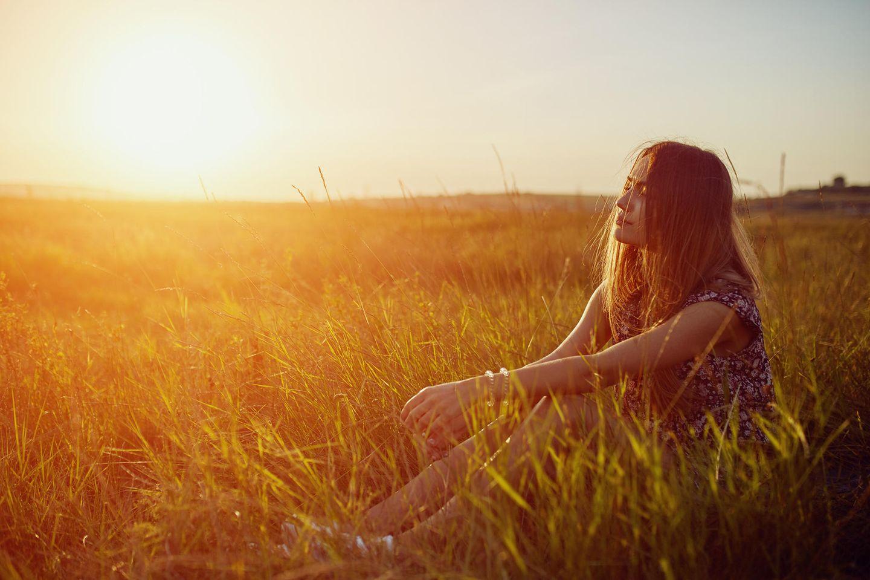 Eine Frau sitzt auf einer Wiese und träumt