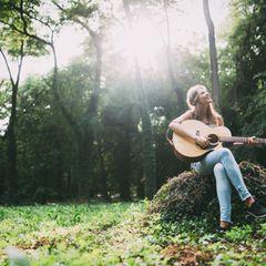 Eine Frau sitzt im Wald mit einer Gitarre