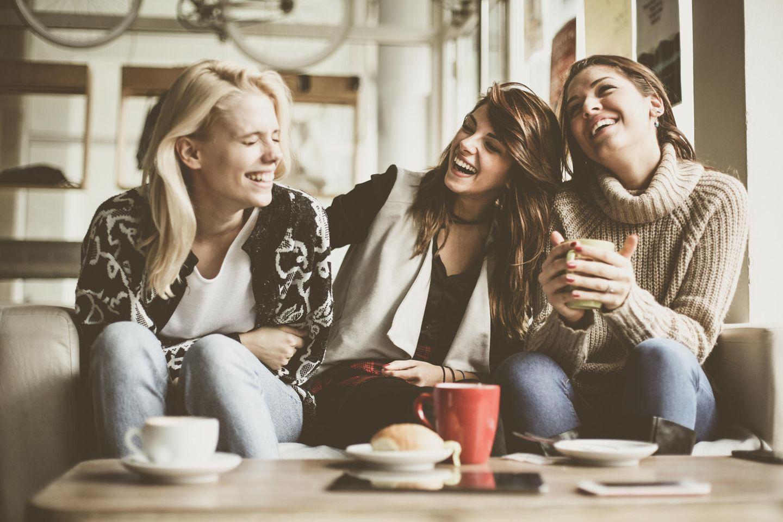 Freundinnen sitzen auf der Couch und lachen