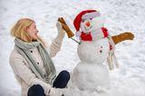 Eine Frau gibt einem Schneemann eine High Five