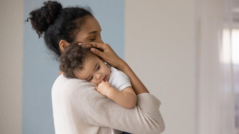 Husten, Schnupfen, Heiserkeit: Mutter umarmt ihr Kind auf dem Arm