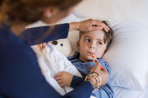 Husten, Schnupfen, Heiserkeit: Junge liegt mit Fieberthermometer im Bett