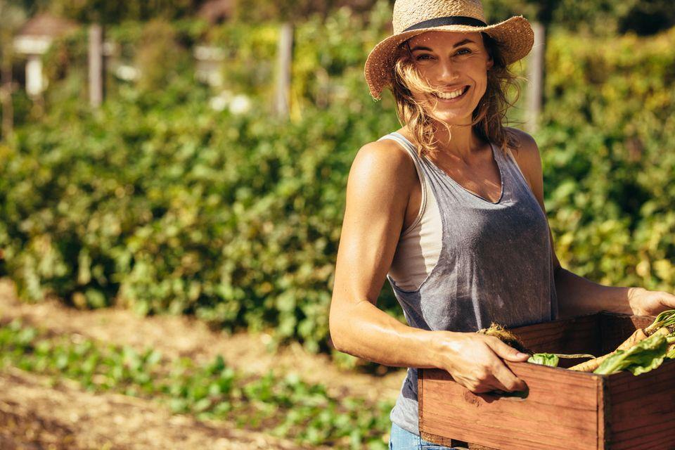 Autark leben: Frau hält Gemüsekiste in der Hand