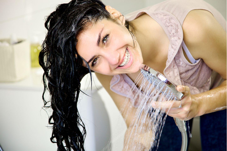 Shampoo ohne Silikone: Frau wäscht sich mit Shampoo die Haare.