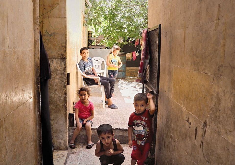 Ein Schal fürs Leben: Kinder vor einem Abbruchhaus