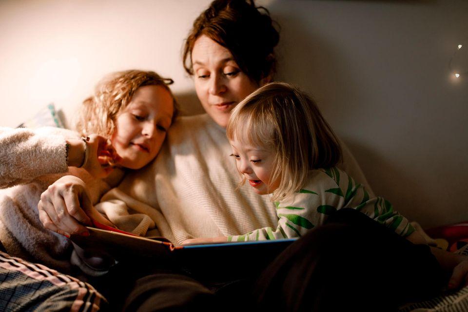 Mama mit zwei Kindern liest vor