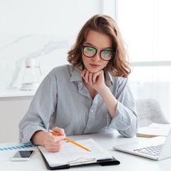 Frau arbeitet konzentriert am Schreibtisch