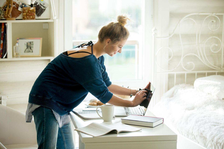Eine Frau putzt in ihrem Schlafzimmer