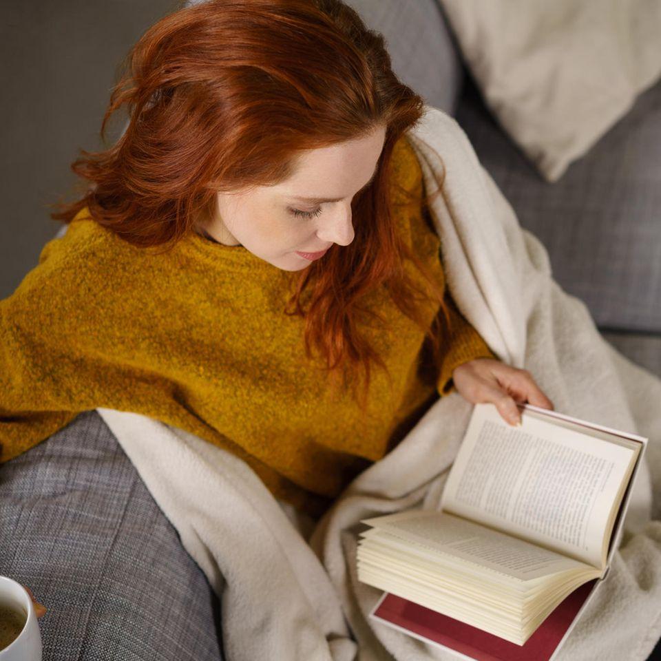 Eine hübsche Frau sitzt auf dem Sofa und liest