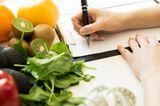 Frau schreibt einen Ernährungsplan