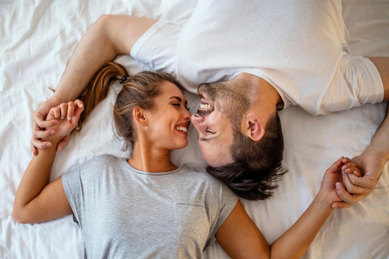 Karezza: Mann und Frau lächeln sich im Bett an