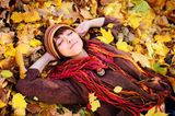 Eine Frau liegt im Herbstlaub