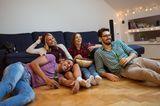 Eine Gruppe von Freunden sitzt vor dem Fernseher und schaut einen Film