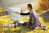 Eine Frau malt ein Bild in einer Herbstlandschaft