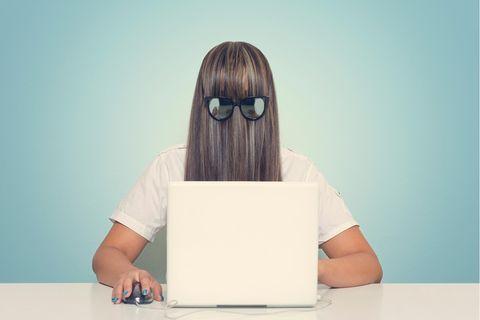 Frau mit Haaren und Brille vor dem Gesicht, sitzt am Laptop