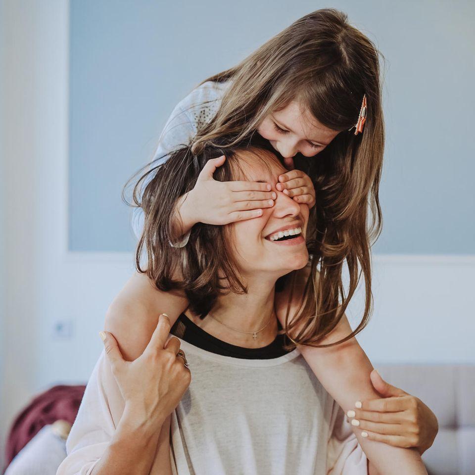 Mehr als Mama: Mädchen auf den Schultern der Mutter