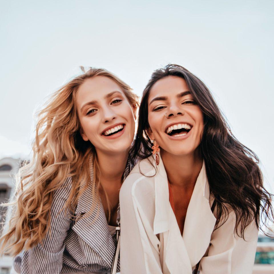 Naturlocken stylen: Zwei lächelnde Frauen mit lockigen Haaren.