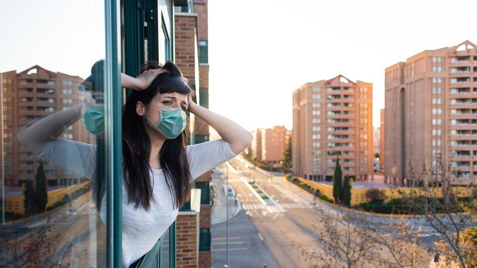 Mann am Fenster mit Mundschutz