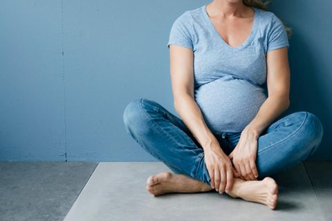 Schwangere Frau vor blauem Hintergrund