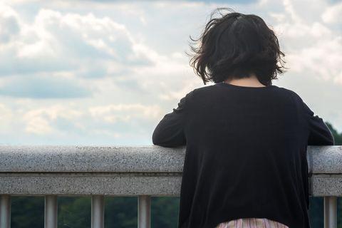 Suizidgedanken: Eine Frau steht am Geländer und denkt nach