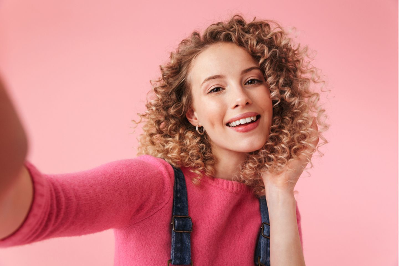 Naturlocken Pflege: Frau mit blondem lockigem Haar vor pinkem Hintergrund.