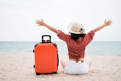 Dahin fahren wir in den Nachbarländern am liebsten: Frau mit Koffer am Strand