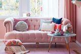 Wer es blushfarben, aber dennoch knallig mag, setzt große Wohnakzente wie dieses Sofa, umhüllt von einem Blush-Teppich und -Vorhängen.