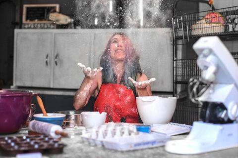 Frau in Küche wirft Mehl nach oben