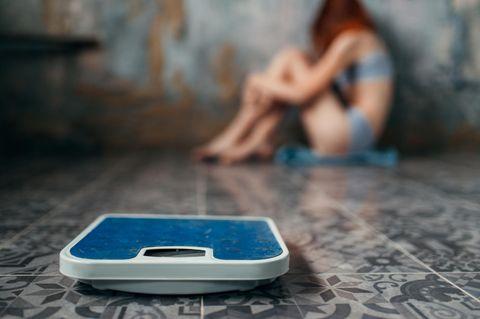 Magersucht: Mädchen kauert auf dem Boden, vor ihr eine Waage