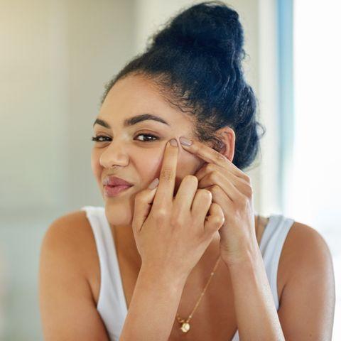 Braunhaarige Frau drückt Pickel im Gesicht