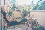 Eine Frau sitzt auf dem Balkon und träumt