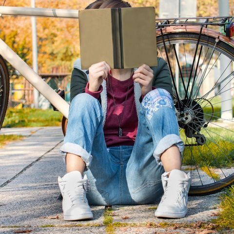 Eine Frau mit Heft und Fahrrad